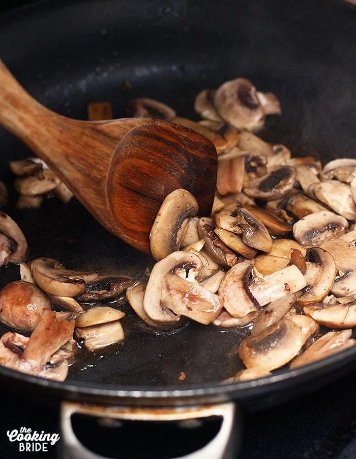 stirring mushrooms in a skillet