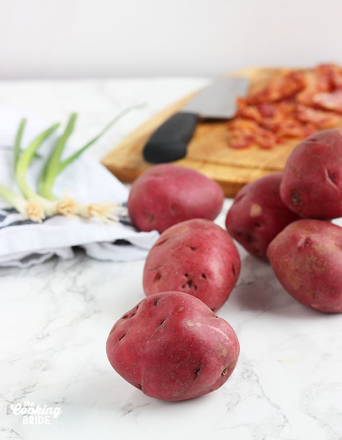 whole red potatoes on a marble background with green onions an bacon in the background