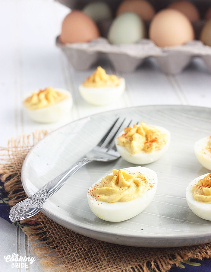 close up of two deviled eggs on a gray plate with a fork in the background
