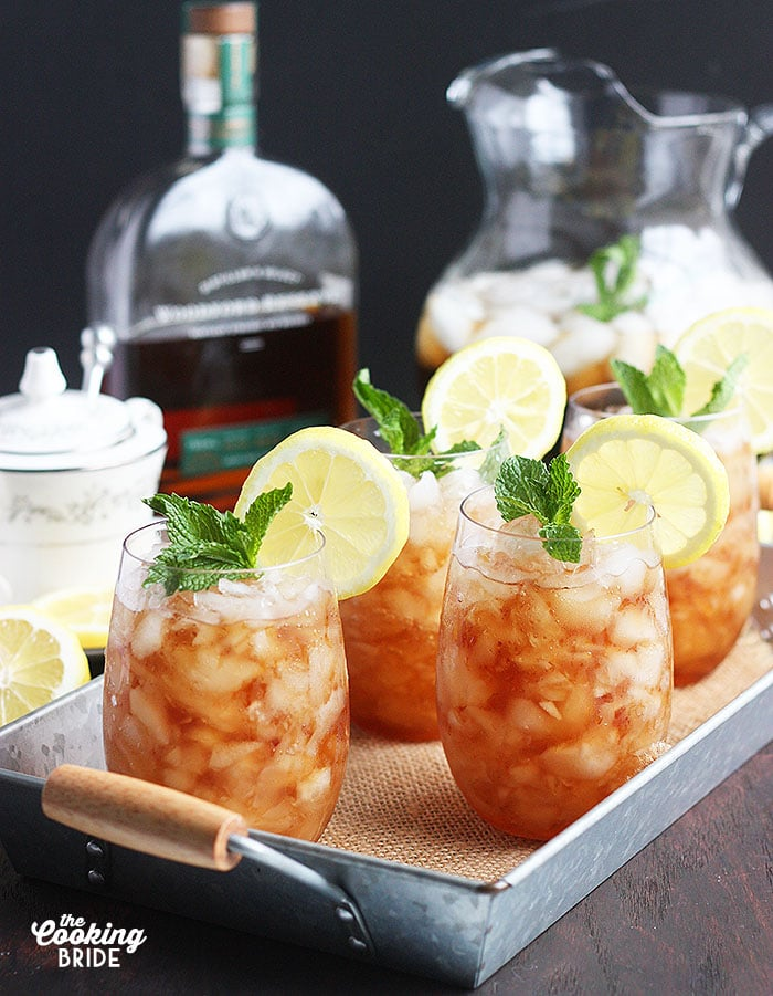 mint julep cocktails on a metal tray with a bottle of bourbon and sweet tea in the background