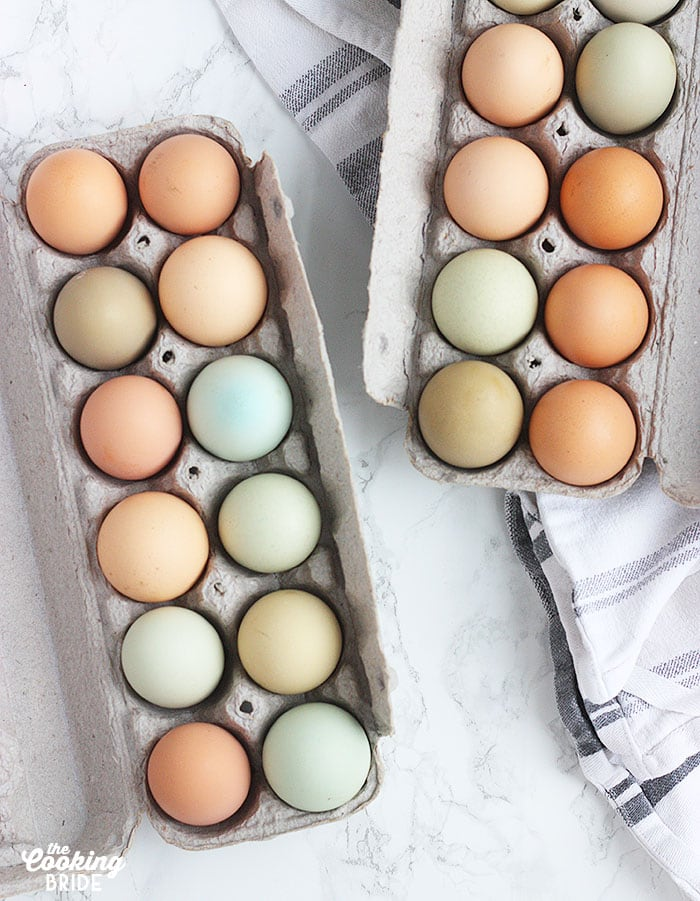 two dozen eggs in paper cartons on a marble background