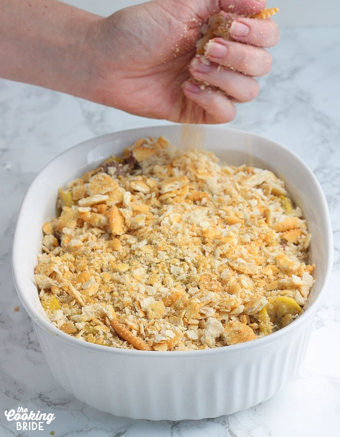 hand crumbling crackers over the top of the casserole