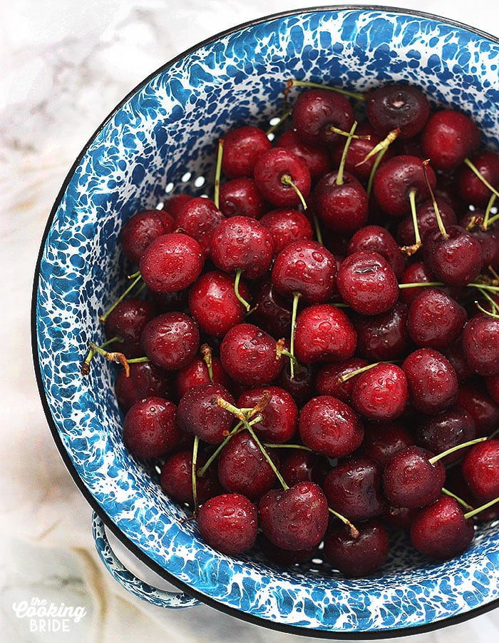 fresh red cherries in a blue and white speckled colander