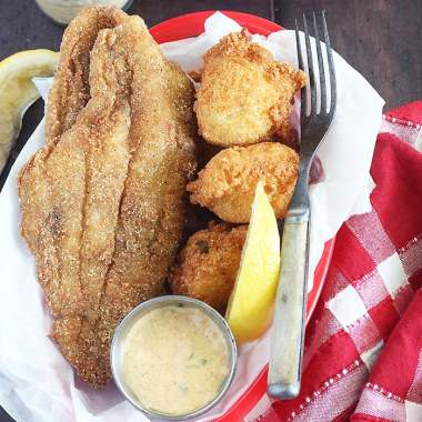 fried catfish fillets in a basket sitting on a red plaid napkin