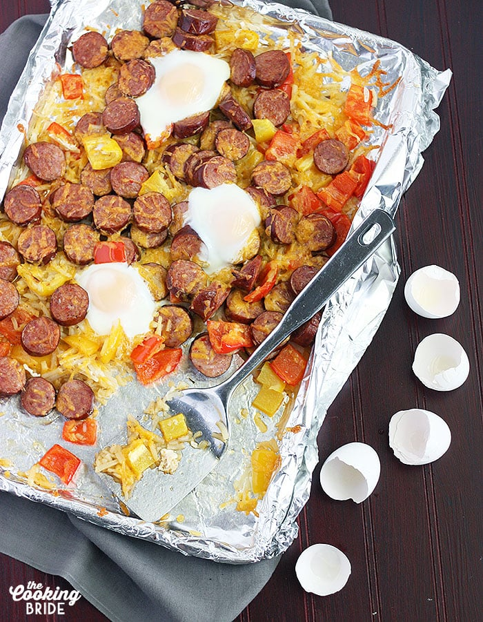 smoked sausage with veggies on a foil line baking sheet and a metal spatula. Cracked egg shells to the side.
