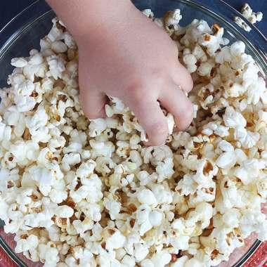 little hand reaching into a glass bowl full of homemade kettle corn
