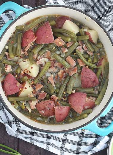 blue pot full of green beans and potatoes with a plate and serving spoon to the side