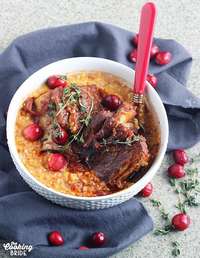 short ribs nestled in corn grits garnished with fresh cranberries and thyme in a white bowl
