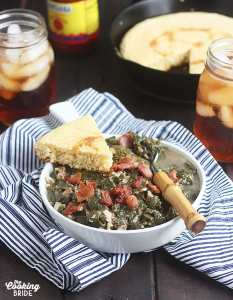 cooked turnip greens topped with bacon and a wedge of cornbread in a white bowl