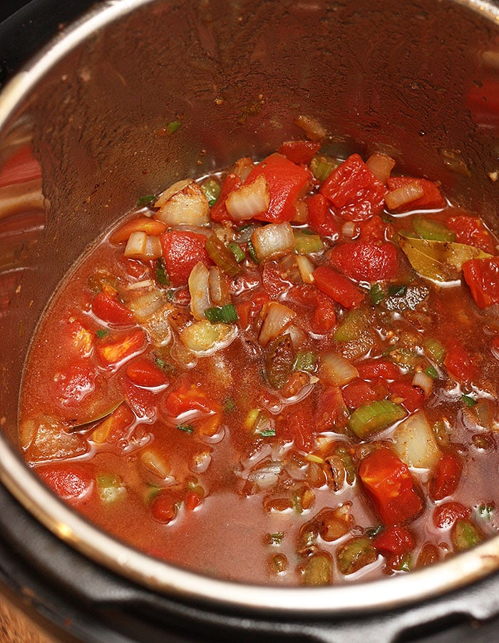 adding tomatoes and beef broth to the pot