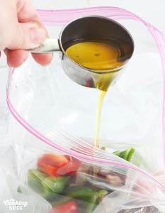 pouring olive oil into a freezer bag full of vegetables