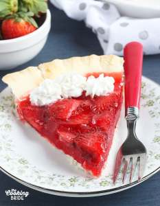 one slice of fresh strawberry pie topped with whipped cream on a floral plate on a blue background