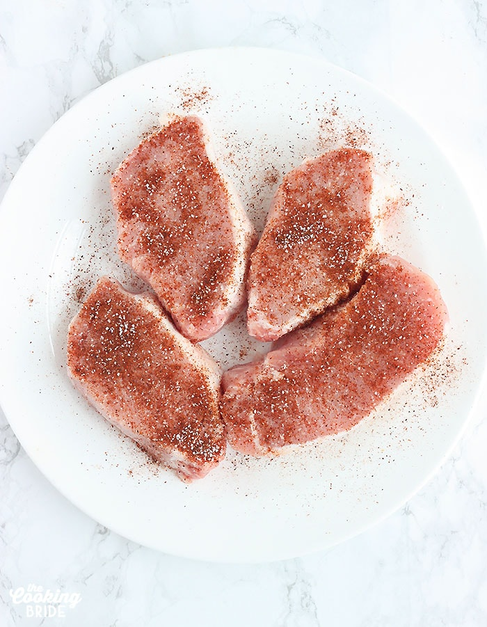 uncooked pork chops sprinkled with seasoning on a white plate