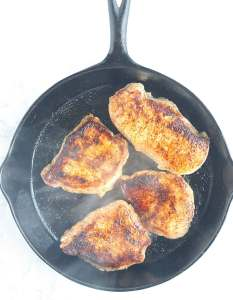 pan frying the pork chops in a cast iron skillet