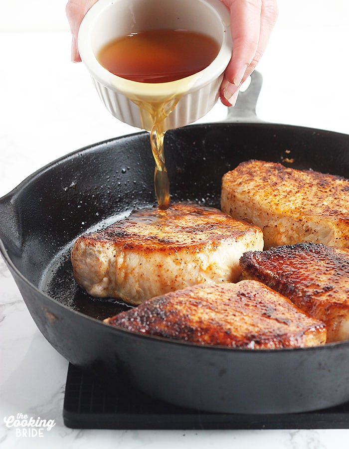 pouring the maple glaze over the pork chops