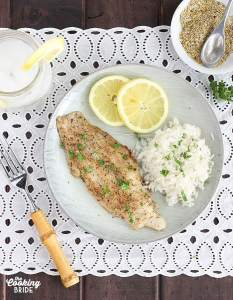 overhead shot of lemon pepper catfish fillet with rice an lemon slices on a gray plate