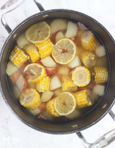 corn, potatoes and lemon slices soaking in a large stock pot of water