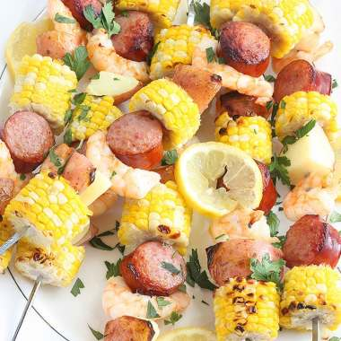 shrimp kabobs with sausage, corn and potatoes threaded on metal skewers on a white platter