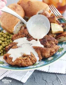 drizzling cream gravy over the top of a country fried steak