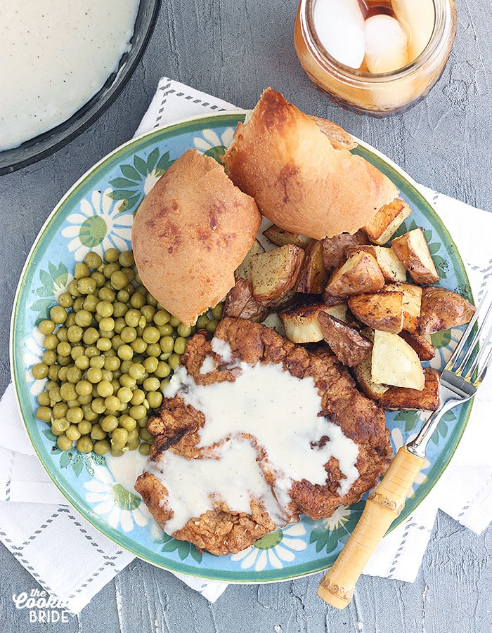 country fried steak with cream gravy on a blue and green floral plate with peas, roasted potatoes and rolls