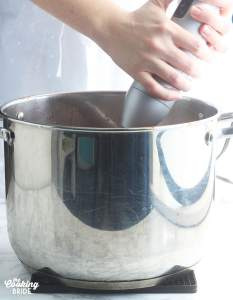pureeing the soup with an immersion blender
