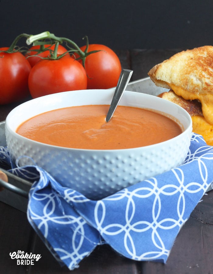 bowl of cream of tomato soup sitting on a tray with a blue napkin underneath