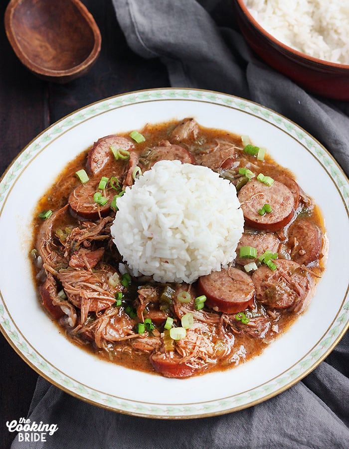 chicken and sausage gumbo with rice in a white bowl trimmed with green leaves