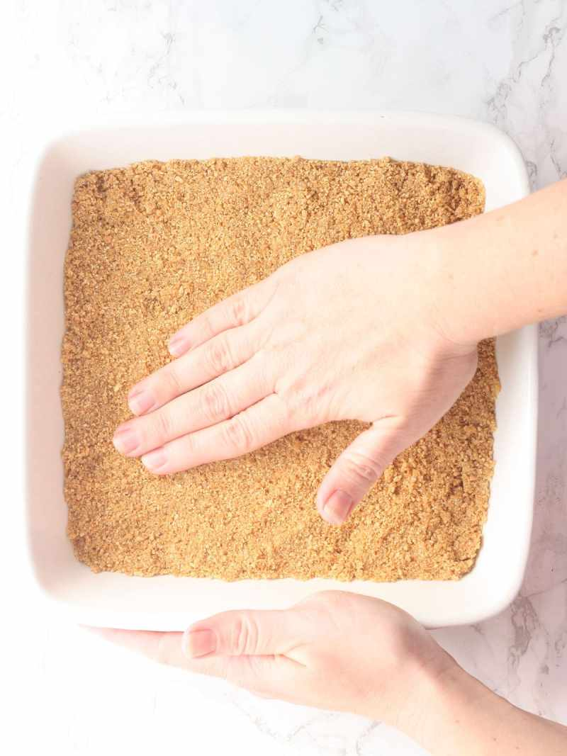 hand pressing graham cracker crumbs into the bottom of an 8 x 8-inch baking dish