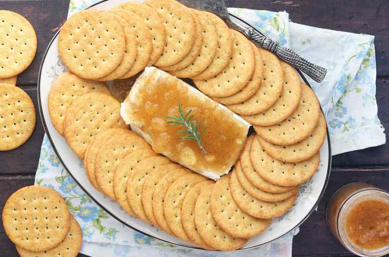 overhead view of block of cream cheese on a floral China plate covered in Jezebel sauce surrounded by crackers