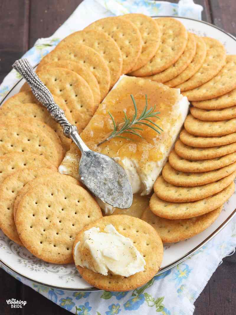 block of cream cheese on a floral China plate covered in Jezebel sauce surrounded by crackers