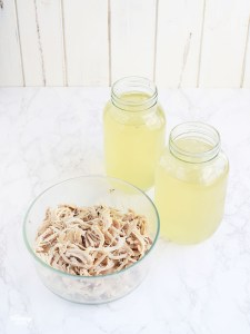 shredded chicken with two jars of broth in the background