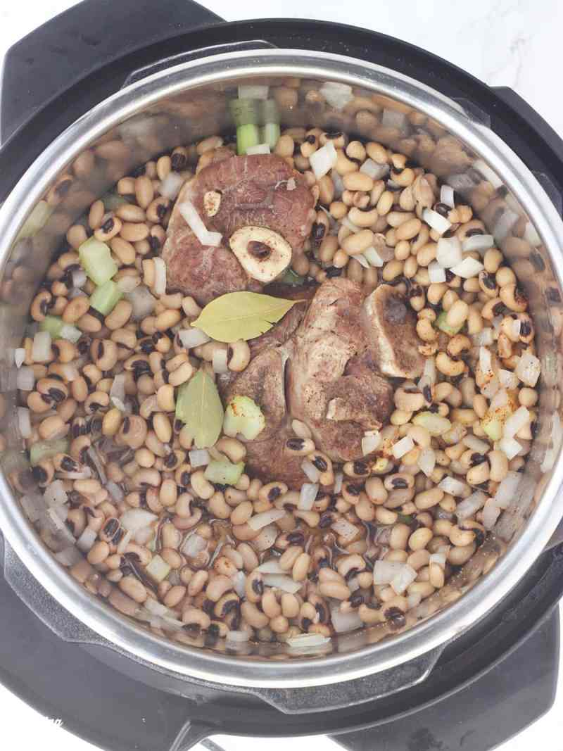 overhead shot of black-eyed peas, ham hock and bay leaves in an Instant Pot