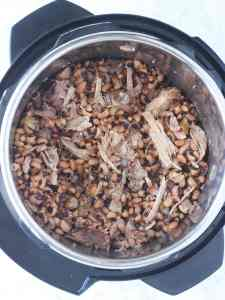 Overhead shot of cooked black-eyed peas with shredded pork in an Instant Pot