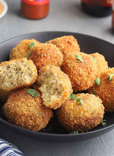 fried boudin balls in a black serving bowl with one broken open to show the inside