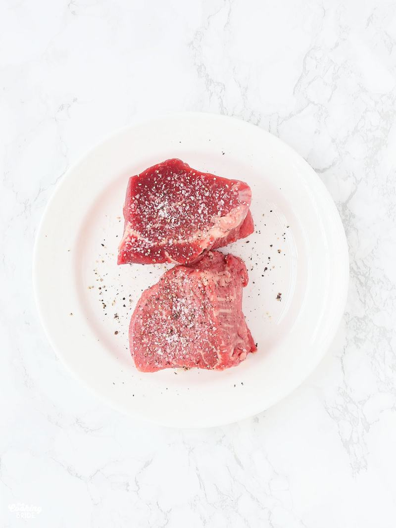 two raw filets seasoned with salt and pepper on a white plate