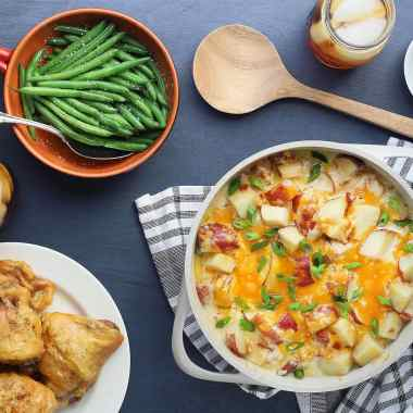 cheesy ranch roasted potatoes in a white casserole dish with fried chicken and green beans on the side