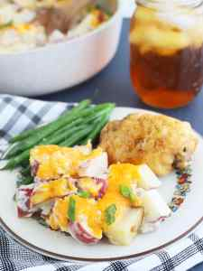 serving of cheesy ranch roasted potatoes on a plate with fried chicken, green beans and a glass of sweet tea in the background