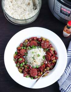 white dish of red beans and rice with a metal spoon, bowl of cooked rice and an Instant pot to the side