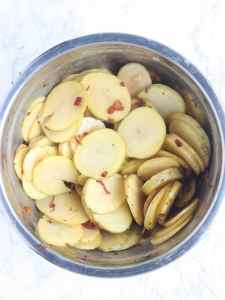 thinkly sliced Yukon gold potatoes in a metal mixing bowl