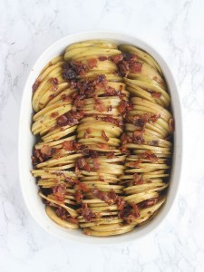 sliced potatoes lined up in a white oval casserole dish and sprinkled with chopped bacon