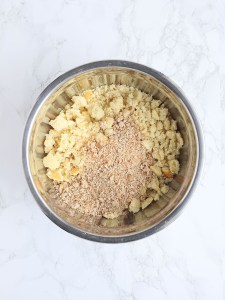 crumbled cornbread and breadcrumbs in a steel mixing bowl