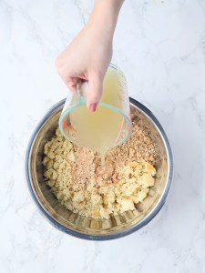 hand pouring chicken broth into a mixing bowl of crumbled cornbread and breadcrumbs