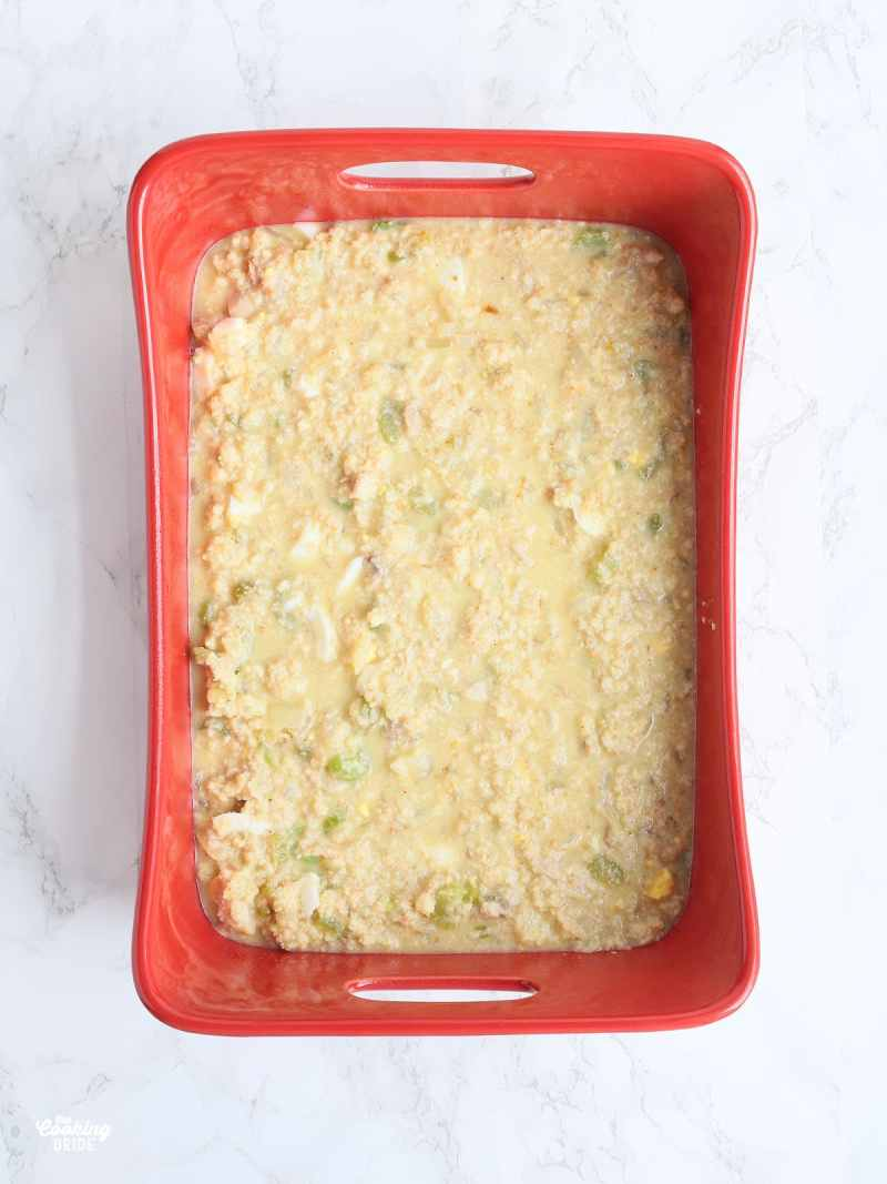 unbaked cornbread dressing in a red baking dish