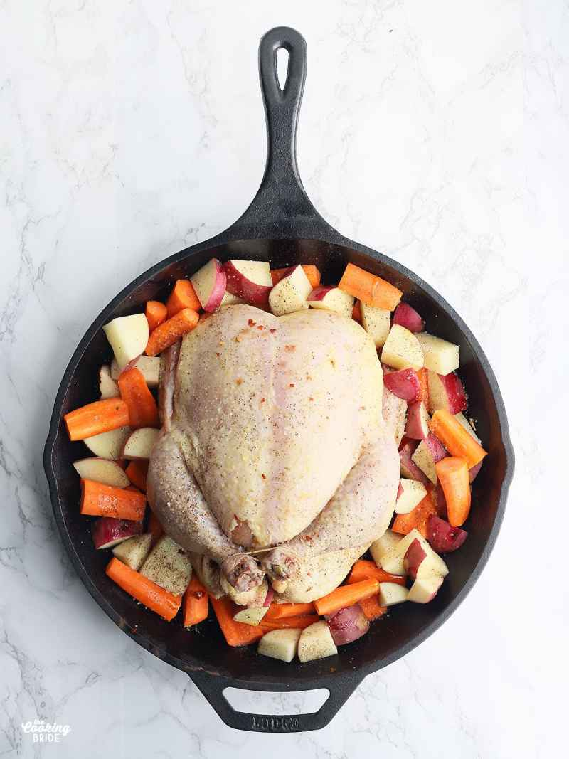 raw while chicken on a bed of chopped carrots and potatoes in a cast iron skillet