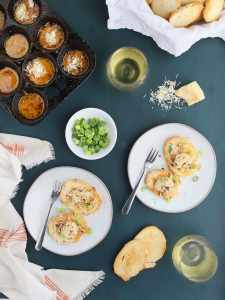 two gray plates with oysters on toast sprinkled with Parmesan cheese, sliced green onions, glasses of white wine, muffin pan of cooked oysters to the side