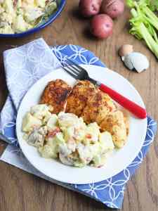 helping of potato salad on a white plate with a serving of roast chicken, a red fork and a blue and white napkin