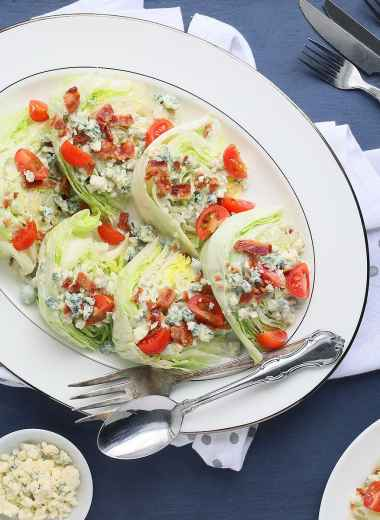 bacon and tomato wedge salads arranged on a white platter with extra blue cheese crumbles, dressing and a plated salad on the side