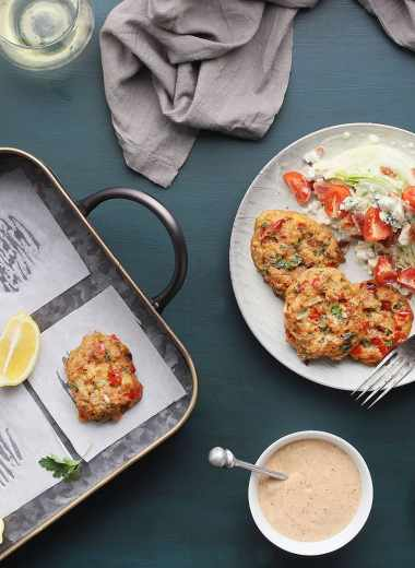 tray of baked crab cakes with condiments and two glasses of white wine to the side