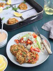 three oven baked crab cakes on a plate with a salad to the side and a tray of crab cakes in the background