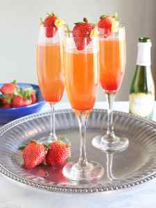 three filled champagne flutes garnished with strawberries on a silver tray